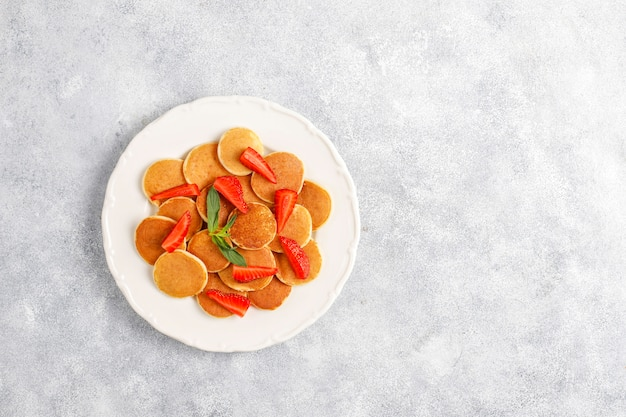 Модная еда - мини блинная каша. куча зерновых блинов с ягодами и орехами.