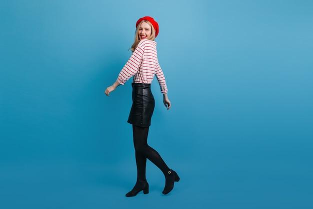 Модная французская девушка, глядя через плечо на синюю стену. чудесная блондинка в короткой юбке.