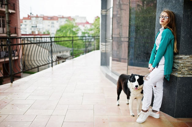 Trendy girl at glasses and ripped jeans with russo-european laika (husky) dog on a leash, against street of city