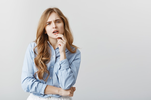 Trendy girl having doubts about new dress. disbelieving good-looking female student in blue-collar shirt, touching lip and staring with concerned expression, thinking over gray wall