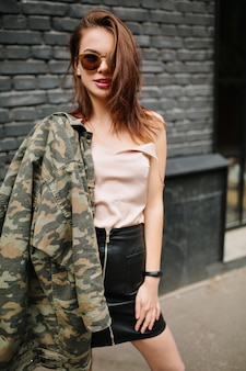 肩にミリタリージャケットを保持し、灰色のレンガの前で自信を持ってポーズをとって暗いサングラスのトレンディな女の子