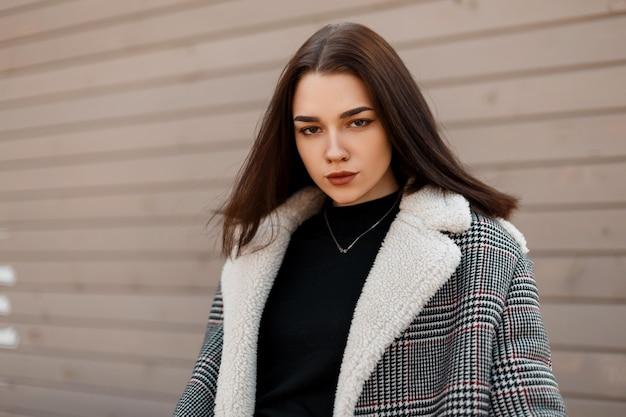 Модная девушка в модной одежде возле деревянной стены