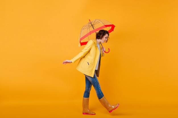 우산과 함께 포즈를 취하는 동안 아래를 내려다 보면서 고무 신발과 노란색 재킷에 유행 소녀. 파라솔과 함께 걷는 청바지에 곱슬 짧은 머리 여자의 스튜디오 샷.