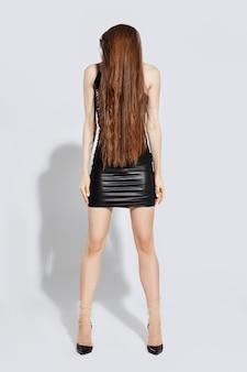 얇은 명주 그물 양말과 에코 가죽 짧은 드레스에 유행 소녀