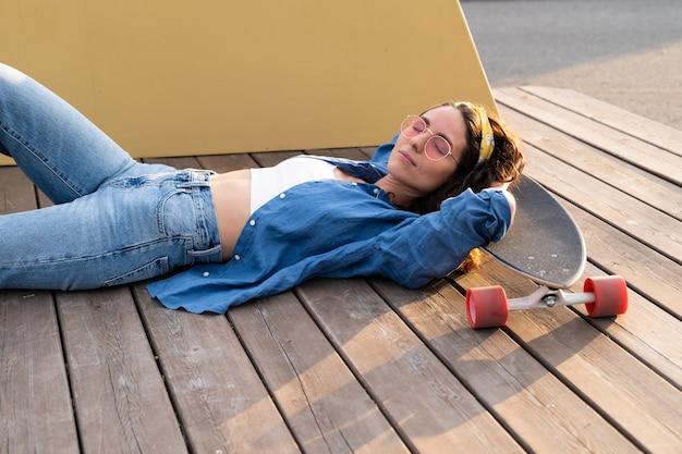 눈을 감고 롱보드에 누워 있는 트렌디한 소녀는 나무 데크에서 여성 스케이트보더의 오버헤드 뷰를 닫았습니다.