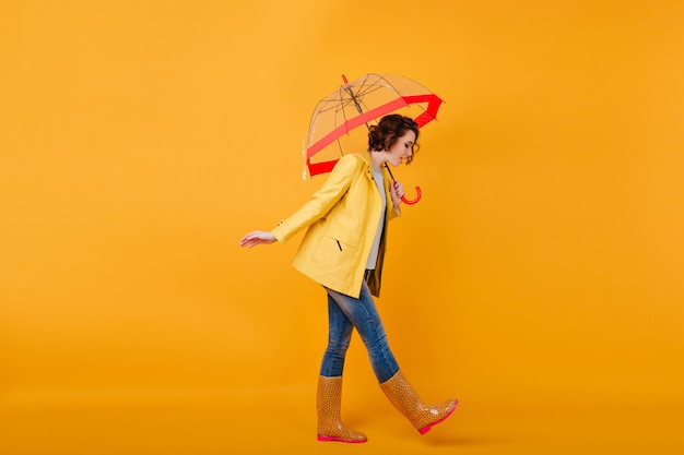 Trendy girl in rubber shoes and yellow jacket looking down while posing with umbrella. studio shot of curly short-haired woman in jeans walking with parasol.