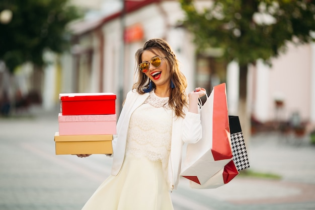 Trendy girl in sunglasses with shoe boxes and shopping bags in t