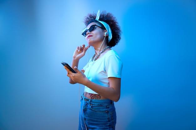 アフロカールを持つトレンディな女の子は、青いネオンの光の中でヘッドフォンで音楽を聴き、楽しんでいます。ヒップホップスタイルのモデルが踊り、リラックスします。