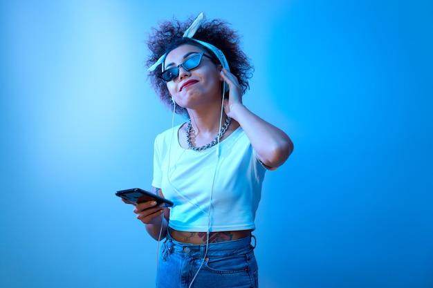 Модная девушка с афро-кудрями слушает и наслаждается музыкой в наушниках в синем неоновом свете, модель в стиле хип-хоп танцует и расслабляется