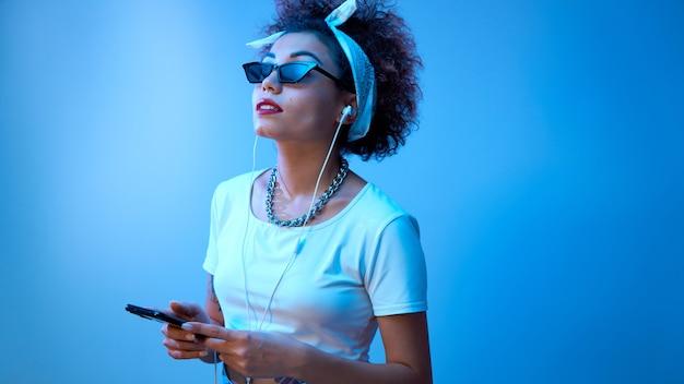 アフロカールを持つトレンディな女の子は、コピースペースのある青いスタジオの背景にスマートフォンとイヤホンを使用し、音楽を聴き、リラックスを楽しんでいます