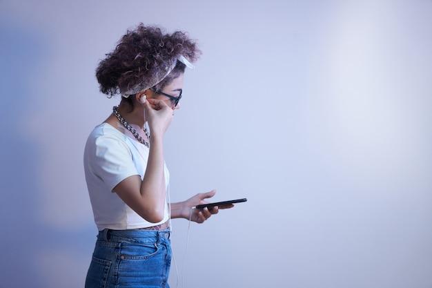 アフロカールを持つトレンディな女の子は、コピースペース、オンライン会話、音楽を聴く青いスタジオの背景にスマートフォンとイヤホンを使用しています