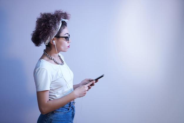 아프로 컬이 있는 트렌디한 소녀는 복사 공간, 온라인 대화, 음악 듣기가 있는 파란색 스튜디오 배경에서 스마트폰과 이어폰을 사용합니다.