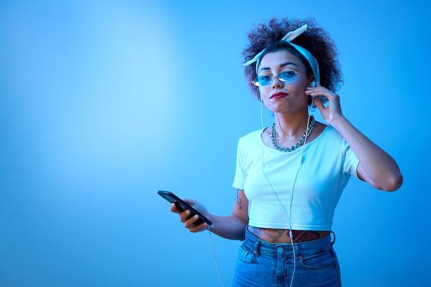 アフロカールを持つトレンディな女の子は、コピースペースのあるスタジオの背景にスマートフォンとヘッドフォンを使用しています