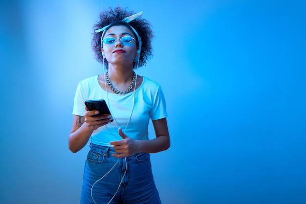 Модная девушка с афро-кудрями использует смартфон и наушники на студийном фоне с копией пространства
