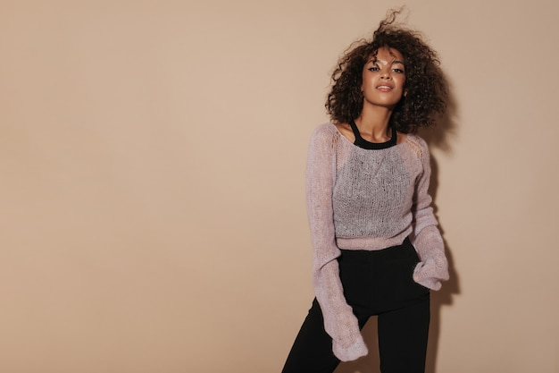 Trendy girl with fluffy curly hair in pink sweater, cool top and black trousers looking into camera on isolated wall..