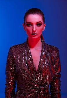 スタジオでネオンの光の中で青い背景にポーズをとる黒い輝くドレスの長い髪とスタイリッシュなメイクのトレンディな女の子