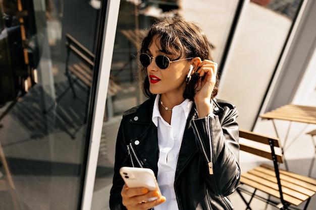 Модная девушка с короткой прической и красными губами в кожаной куртке и черных очках слушает музыку и использует смартфон в солнечном свете на фоне города