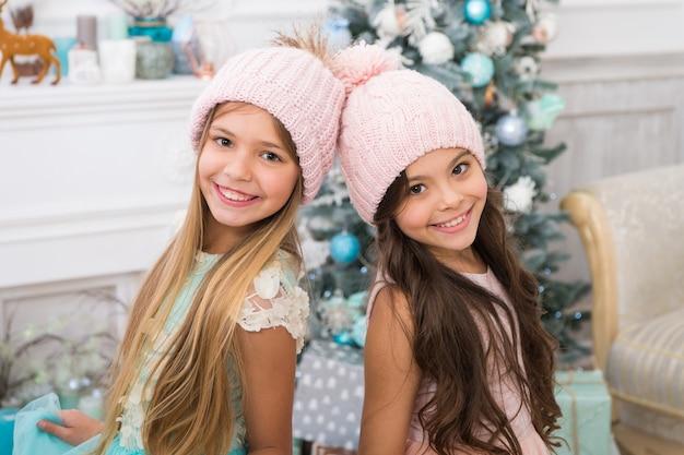 트렌디한 소녀들. 겨울 시즌 액세서리입니다. 아이들은 니트 모자를 쓰고 있습니다. 여자 긴 머리 행복 웃는 얼굴 크리스마스 트리 배경. 아이들은 따뜻하고 부드러운 분홍색 니트 모자를 착용합니다. 소녀들을 위한 멋진 니트 모자.