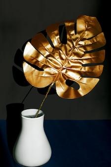 Trendy gold tropical monstera leaf  in white vase on black background