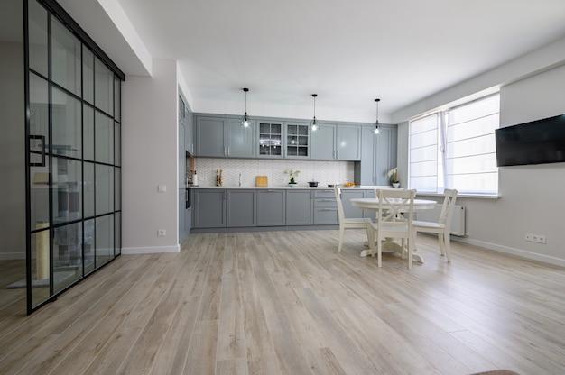 スタジオアパートのトレンディなグレーと白のモダンなキッチン家具