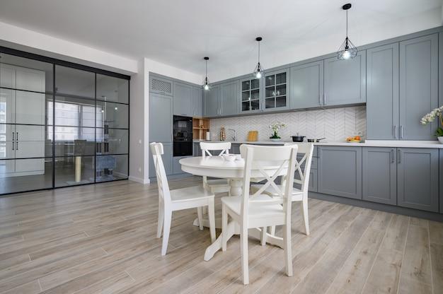 Модная серо-белая современная кухонная мебель в однокомнатной квартире