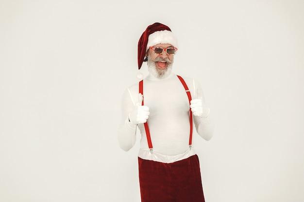 トレンディな白髪のサンタ。男はニットの服を着ます。サンタの帽子をかぶったおじいさん。