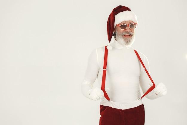 Babbo natale dai capelli grigi alla moda. l'uomo indossa vestiti a maglia. nonno in un cappello di babbo natale.