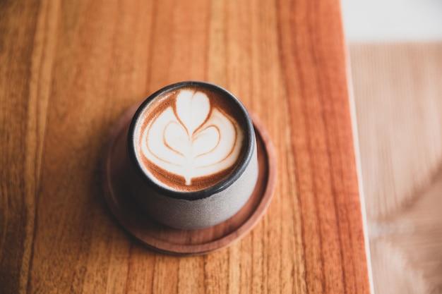 Модная серая стильная чашка горячего капучино с латте-арт на фоне деревянного стола.
