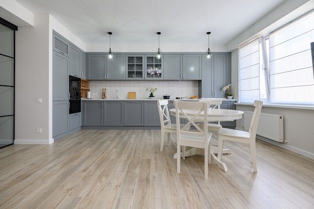 Trendy grey and white modern kitchen furniture in studio apartment