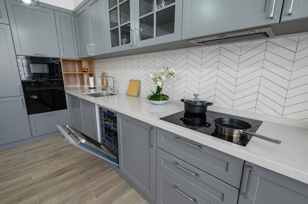 Trendy grey and white modern kitchen furniture with ovens door open
