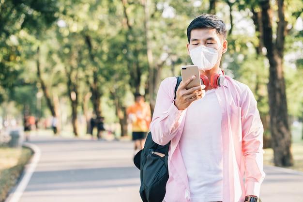 トレンディな男はサージカルマスクを着用し、公共の公園で彼の友人とのコミュニケーションと接続されたソーシャルメディアにスマートフォンを使用しています