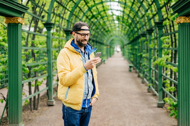 Trendy guy with beard and moustache wearing anorak, jeans and cap standing sideways having attentive look into his smartphone