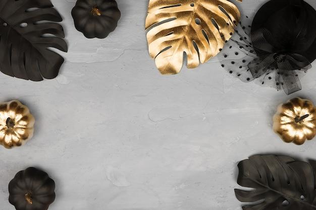 黄金の光沢のある装飾的なカボチャと葉を持つトレンディなハロウィーンのフレーム