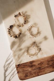 Модные серьги ручной работы и цветочная ветвь на мраморной доске на белом