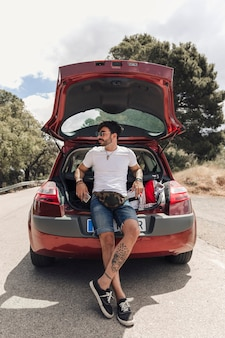 Trendy handsome young man with tattoo leaning on car trunk
