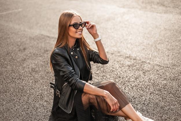 세련 된 선글라스에 세련 된 옷에 아름 다운 미소로 트렌디 한 행복 젊은 hipster 여자는 포장 도로에 앉아서 밝고 화창한 날을 즐깁니다. 귀여운 즐거운 소녀 모델은 야외에서 쉬고 있습니다.
