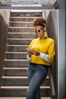 Trendy hipster black woman in headphones browsing smartphone