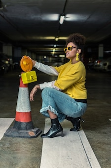Trendy hipster black woman squatting near traffic cone