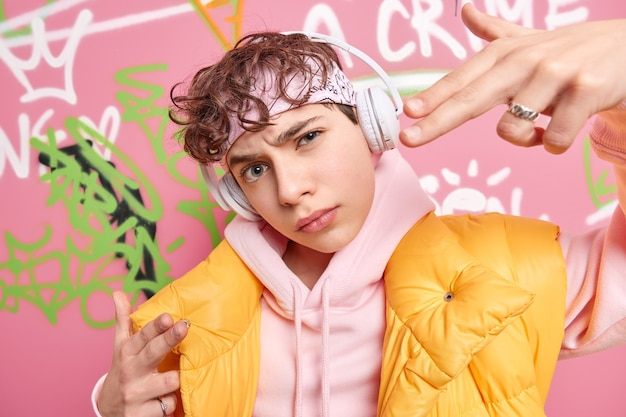 Trendy hipster guy makes yo gesture feels cool while listening rap music via wireless headphones has curly hair wears fashionable hoodie and yellow vest poses against graffiti wall