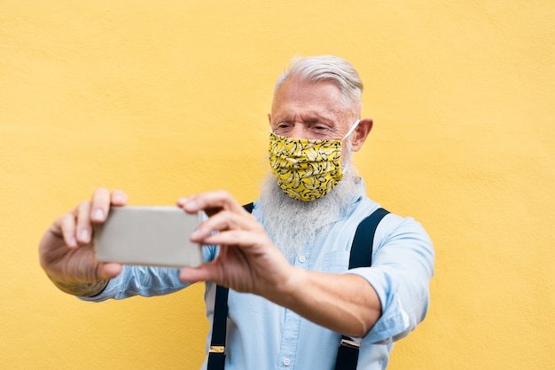 패션 실크 안전 마스크를 착용하는 동안 화상 통화를하는 휴대 전화를 사용하는 유행 힙 스터 남자