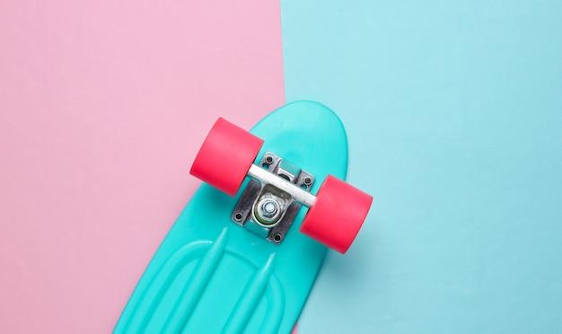 ピンクブルーのパステルカラーの背景に流行のヒップスタースケートボード。ミニマリズムの概念。若者のライフスタイル。