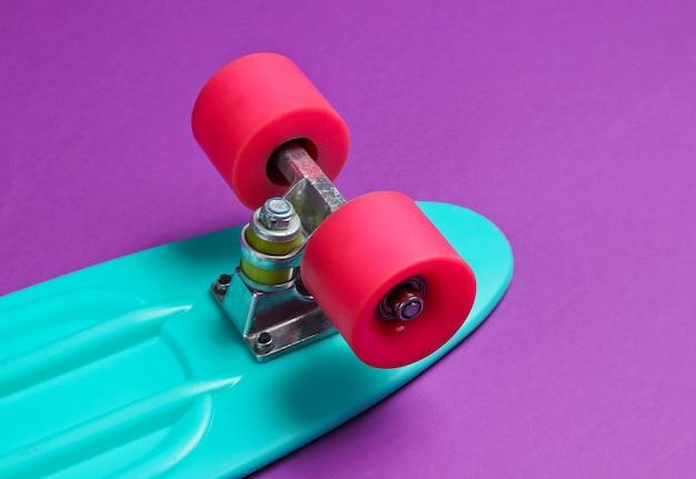 紫色の背景に流行のヒップスタースケートボード。ミニマリズムの概念。若者のライフスタイル。