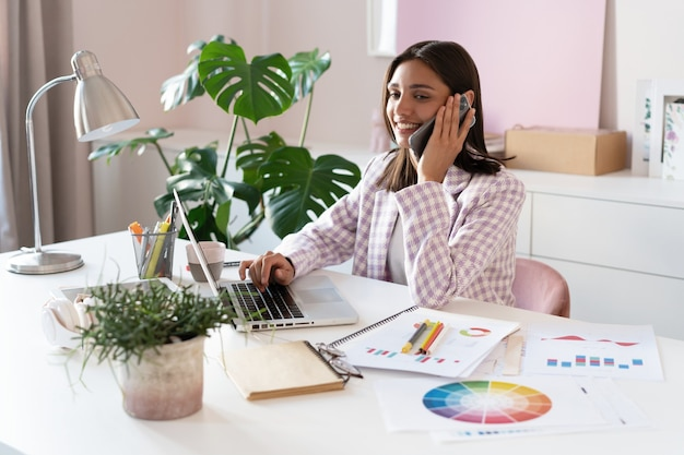 Trendy home office businesswoman talking on phone.