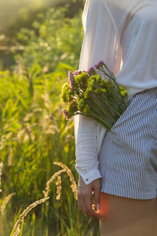 彼女のポケットに花を持つ顔のない女性のトレンディなイメージ-自然への近さと自然の美しさの概念