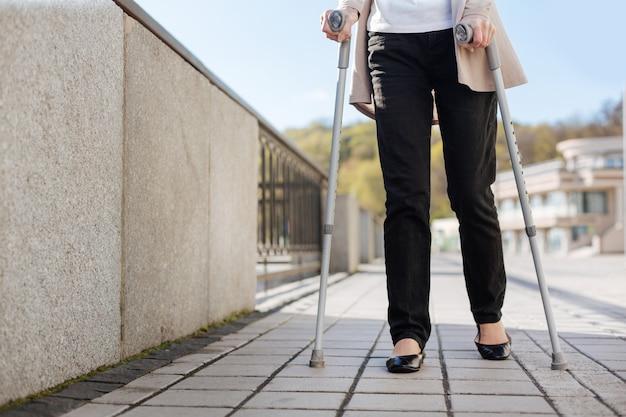 트렌디 한 수줍은 아가씨가 손에 목발을 들고 부두를 따라가는 동안 발걸음을 옮깁니다.