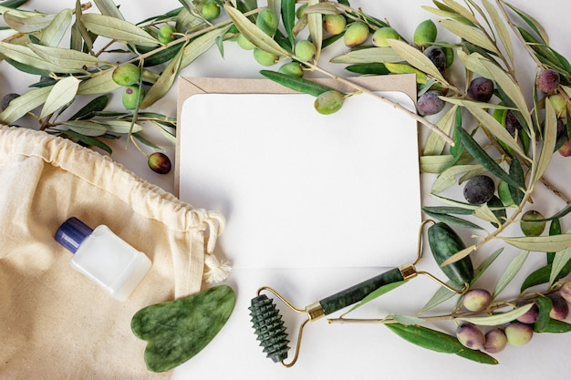 올리브 가지, 유기농 면 가방, 작은 흰색 액체 병, 복사 공간 카드가 있는 천연 흰색 배경에 트렌디한 옥 롤러와 구아 샤 그린. 평평한 평지, 평면도.