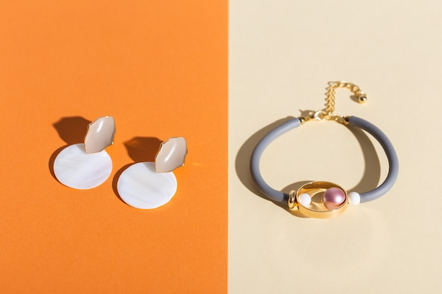 Trendy jewelry on coloured surface