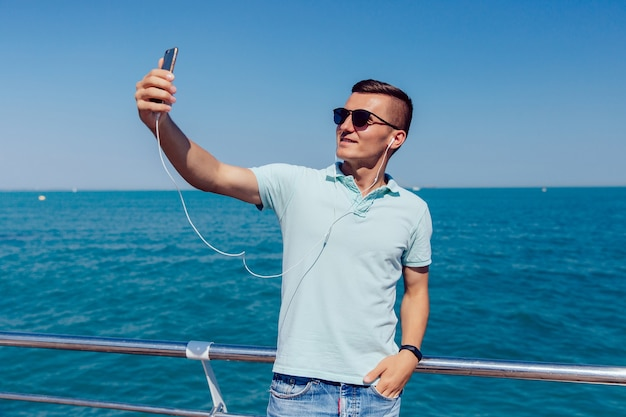 Trendy joyful guy in sunglasses and headset takes a selfie on mobile phone