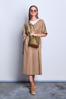 灰色の背景にポーズレザーハンドバッグとストライプオリーブドレスを着て大きなサングラスでトレンディな女性