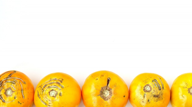 Trendy large ugly organic yellow tomatoes on a white background